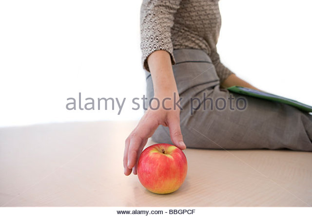 Businesswoman with apple, mid section, cut out - Stock Image