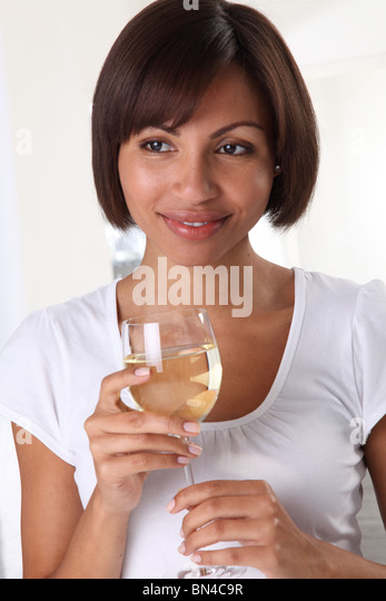 WOMAN HOLDING A GLASS OF WHITE WINE - Stock Image