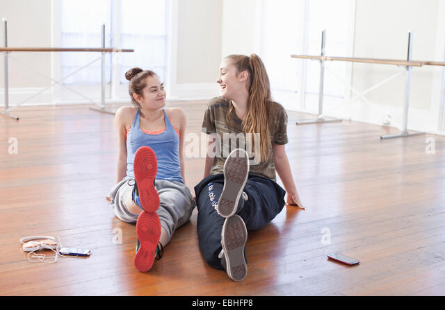 Two teenage girls chatting in ballet school - Stock Image