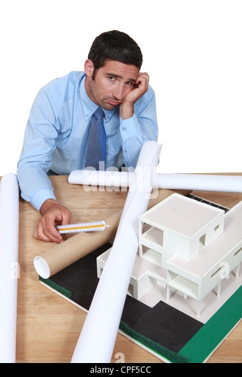 Dejected architect sitting at his desk - Stock Image