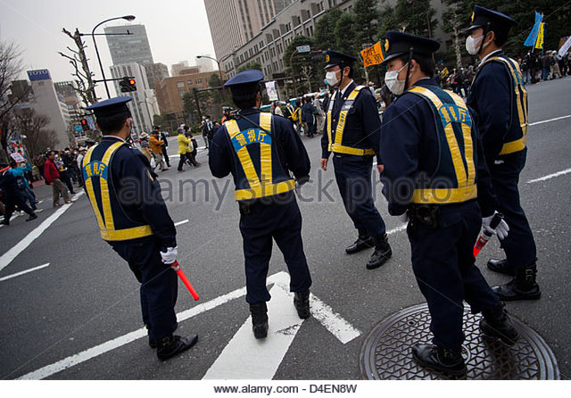 Police watch as tens of thousands of protesters march on the Japanese parliament to demand the government abandon - Stock Image