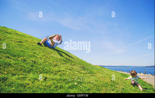 Two boys (2-3, 3-4)  rolling down grassy hill - Stock Image
