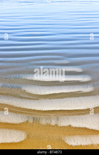 Wet sand texture on ocean shore formed by gentle waves - Stock Image