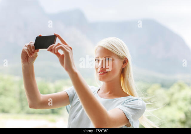 Woman taking pictures in rural landscape - Stock Image