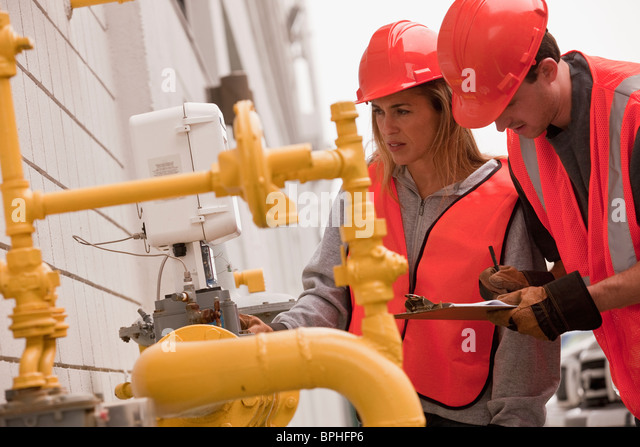 Process engineers taking meter reading near pipeline - Stock Image