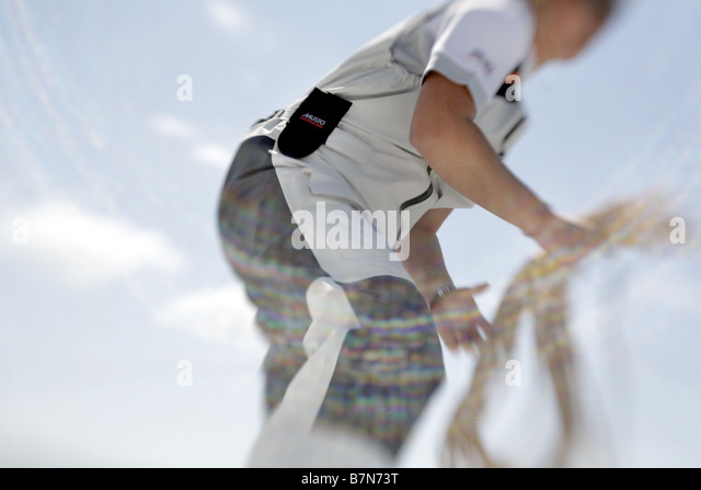 solo sailor skippering a racing yacht - Stock Image