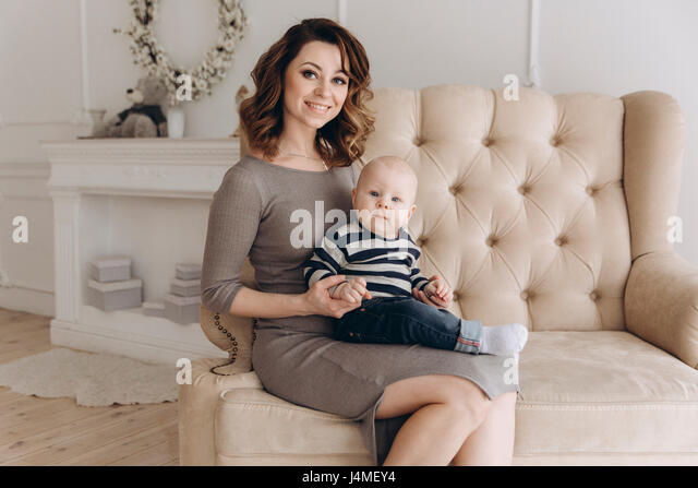 Portrait of Caucasian mother sitting on love seat with baby son - Stock-Bilder
