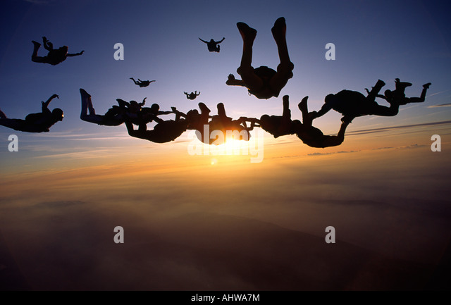 Skydivers are coming together during a sunset Skydive in Switzerland - Stock Image