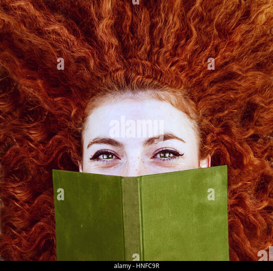 Young redhead woman reading a book - Stock Image