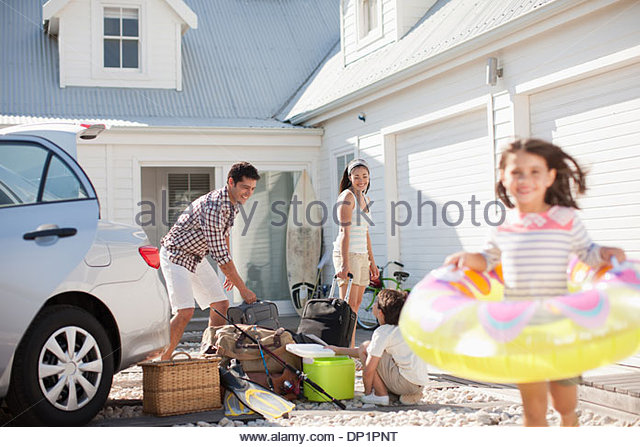 Girl with inflatable ring running in driveway - Stock Image