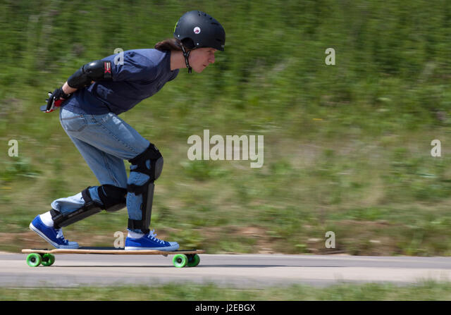 Longboarders race downhill on a closed cycle racing circuit - Stock Image