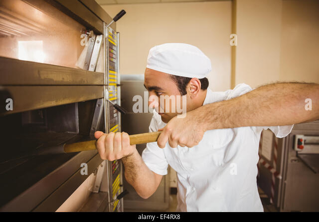 Baker taking bread out of oven - Stock Image