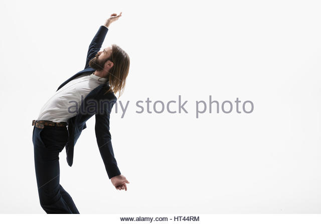 Cool businessman with beard dancing against white background - Stock-Bilder