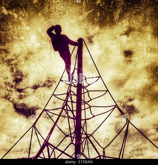 Young boy at  the top of playground climbing apparatus - Stock-Bilder