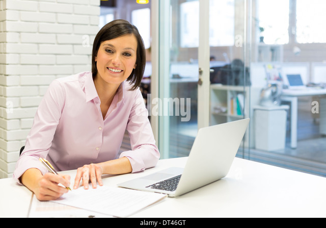 Female pretty young business happy computer desk - Stock Image