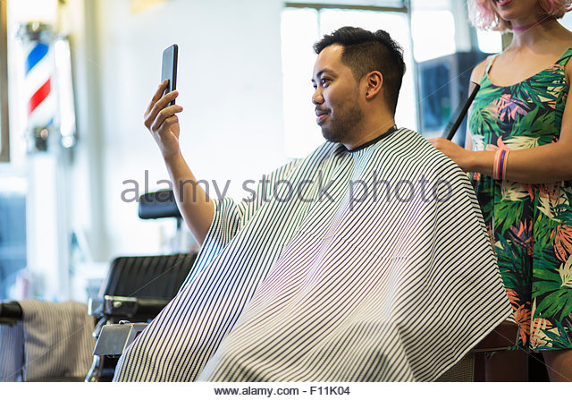 Asian man taking selfie of haircut in retro barbershop - Stock Image