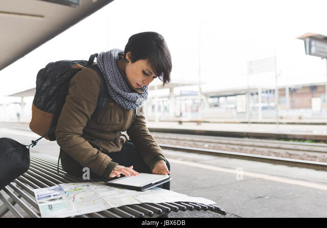 Female backpacker looking at map and digital tablet on railway platform - Stock-Bilder
