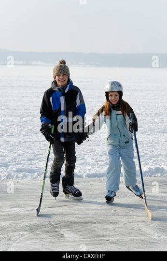 Girl and boy playing ice hockey, near St. Heinrich, Lake Starnberg, Five Lakes region, Upper Bavaria, Bavaria - Stock Image