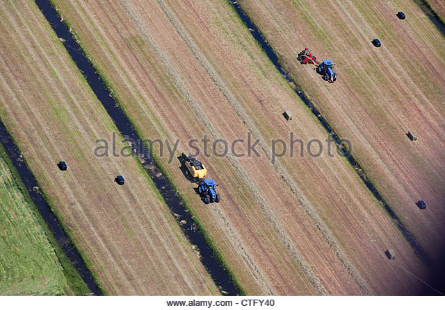 The Netherlands, Loosdrecht, tractors in farm, collecting grass. Aerial. - Stock Image