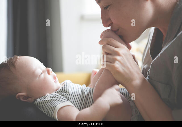 Mother holding and kissing little baby's feet - Stock Image