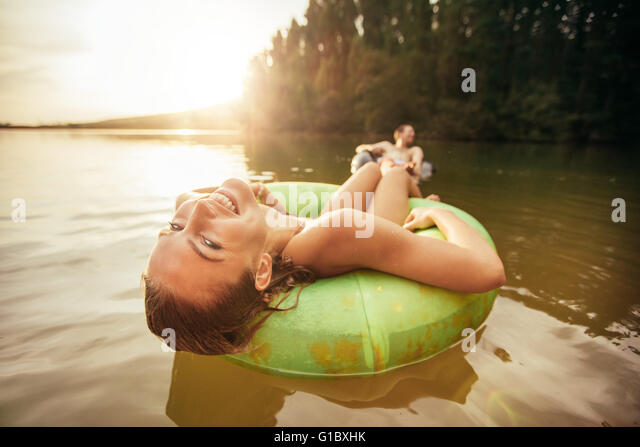 Closeup portrait of smiling young girl floating in an innertube with a man at the background in a lake. Young woman - Stock Image