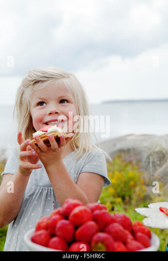 Sweden, Uppland, Roslagen, Girl (6-7) eating strawberry dessert outdoors - Stock Image