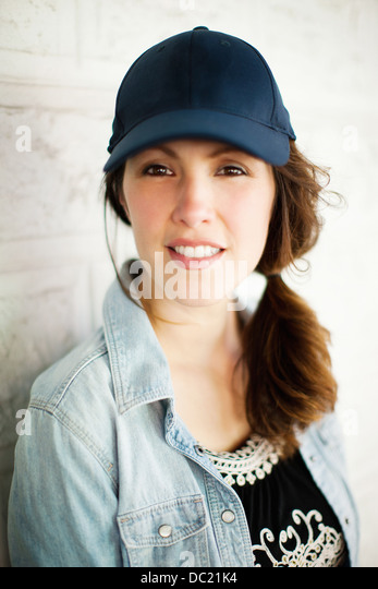 Mid adult woman wearing cap and smiling, portrait - Stock Image