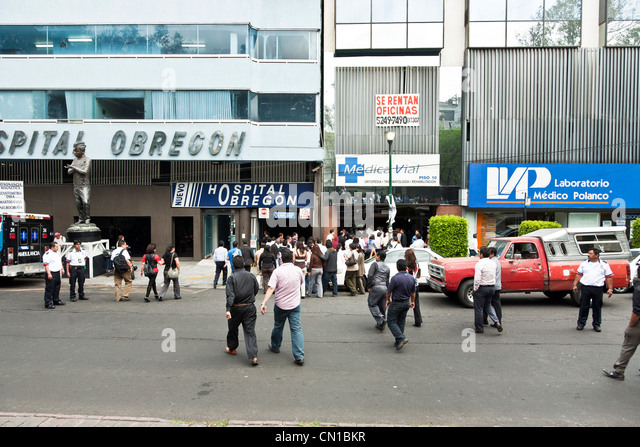 hospital workers staff stream back in to Hospital Obregon & medical buildings Mexico City after earthquake alarm - Stock Image