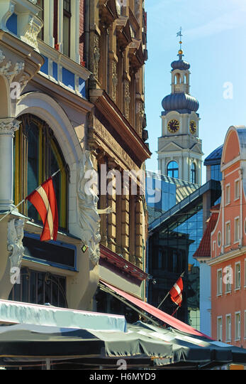 Bas-relief ancient woman on the facade of a historic building in the background the tower of City Hall with a clock - Stock Image