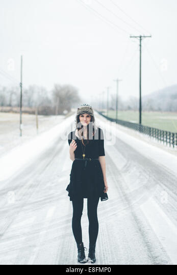 Young woman standing in the road in winter - Stock Image