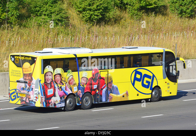 Advertising promoting adventure travel for school children on side and back of coach driving along motorway - Stock-Bilder