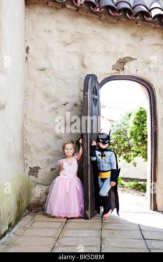 Girl in princess costume and boy in batman costume playing - Stock Image