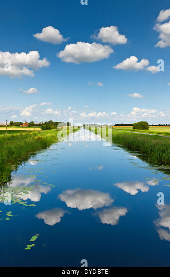 Fluffy white clouds over the sixteen foot drain in Cambridgeshire fenland. - Stock Image