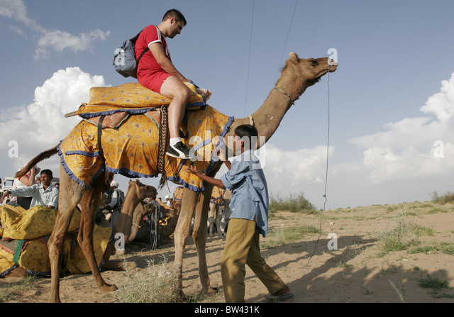 Tourists enjoy a camel ride at Sam, Jaisalmer, Rajasthan, India - Stock-Bilder