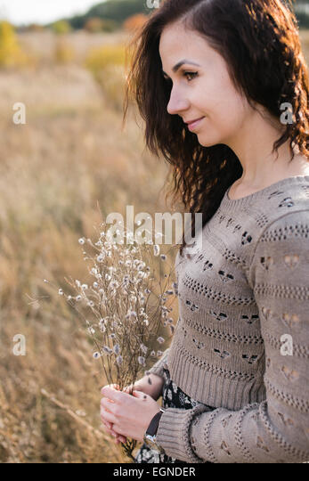 Portrait of a young woman holding a nice bouquet made of dry flowers - Stock-Bilder