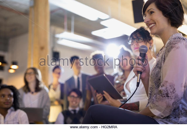 Smiling businesswoman with microphone and digital tablet leading conference meeting - Stock Image