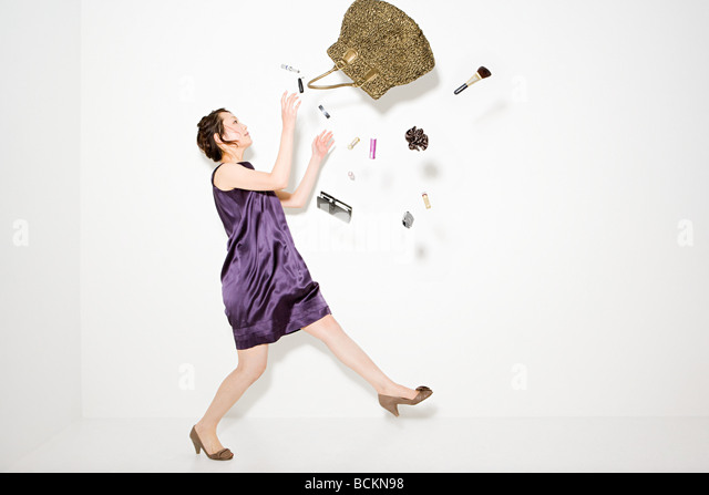 Woman and objects falling out of handbag - Stock Image