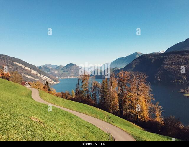 Path on the green hill with trees, lake and mountain - Stock Image