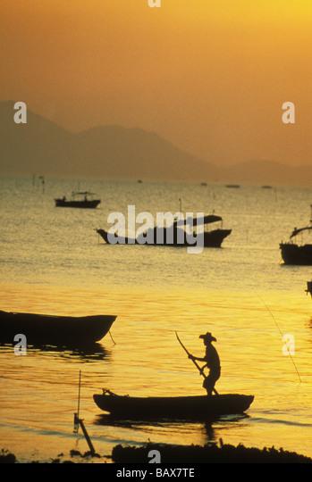 Man poles sampan at sunset at Lao Fao Shan Hong Kong China - Stock Image