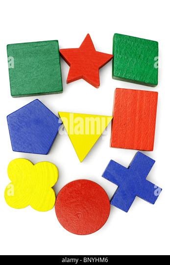 Assorted geometric blocks arranged on white background - Stock Image