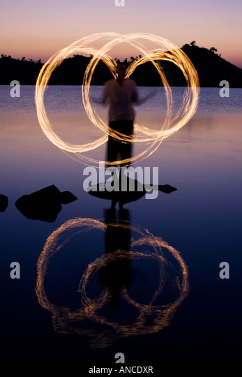 Man fire dancing on a rock in a lake in India - Stock-Bilder