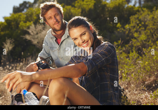 Portrait of happy young woman with her boyfriend taking a break on a hike. Couple hiking on summer vacation, Woman - Stock-Bilder