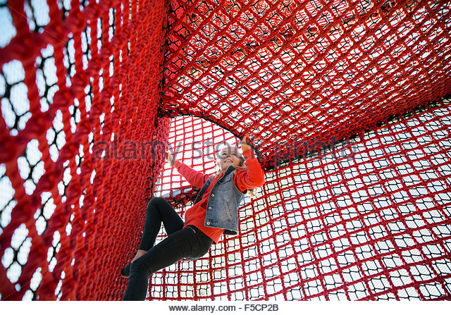 Girl climbing rope net at playground - Stock Image