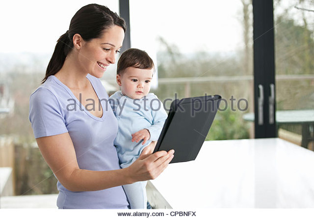 A mother and baby son looking at a digital tablet - Stock Image