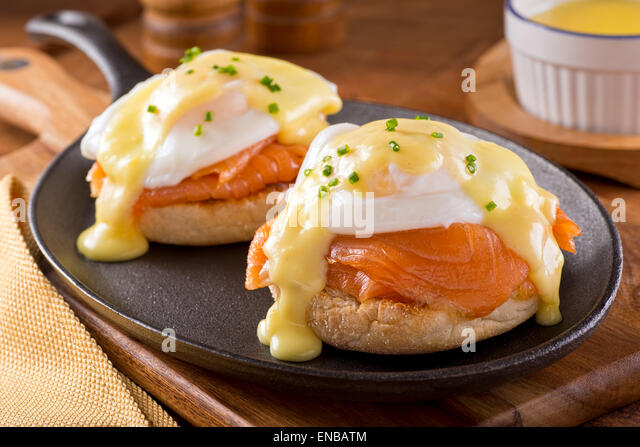 A delicious eggs benedict with smoked salmon, hollandaise sauce, and chives. - Stock Image
