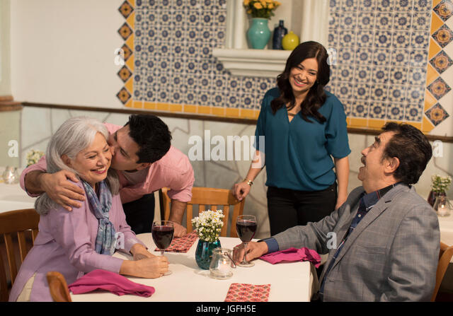 Younger couple greeting older couple in restaurant - Stock Image