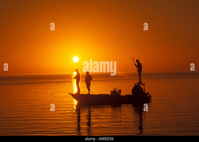Florida Keys sunset bonefishing flats fishing  orange sky silhouette boat guide pole poling islamorada island - Stock Image