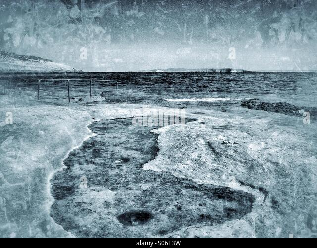 Sea eroded limestone beach looking east towards Comino - Stock Image