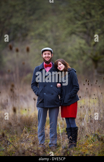 Portrait of a happy couple engaged to be married in the winter outdoors. This couple is modern, trendy, hipster, - Stock Image