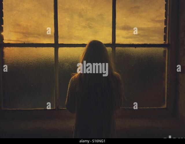 Blonde woman looking at sunset from the window - Stock-Bilder